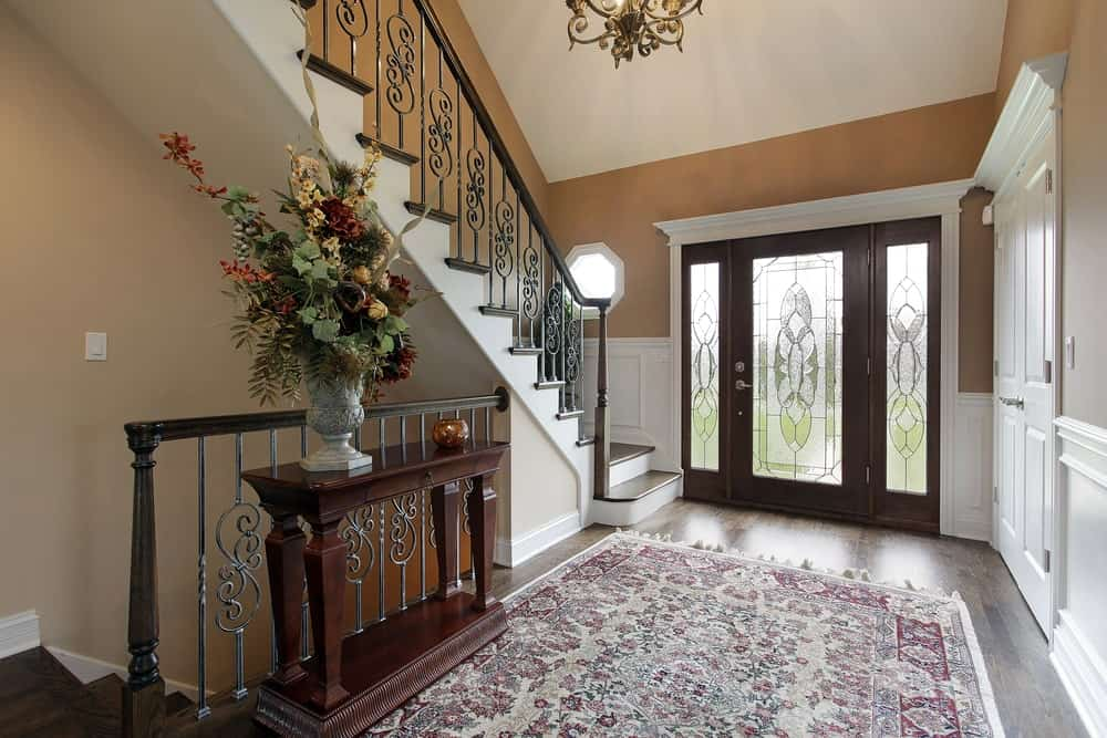 The main door and its side lights are dominated by large frosted glass panels with elegant designs on it. This is matched with a colorful patterned area rug just inside the foyer upon entry of the dark hardwood flooring. This matches with the wooden console table that bears decors.