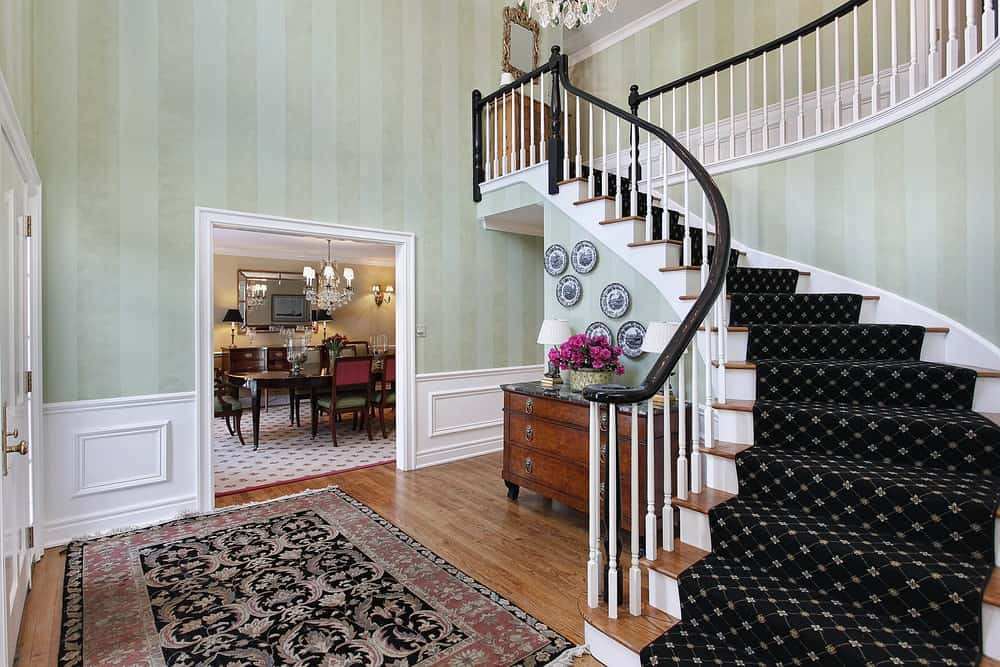 The light green striped wallpaper is complemented by the white wainscoting with an elegant finish. This is contrasted by the dark patterned area rug covering most of the hardwood flooring and the staircase.