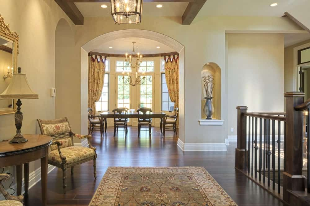 This elegant Farmhouse-style foyer has beige walls and beige ceiling that has exposed wooden beams that match the hardwood flooring that is topped with a patterned area rug that goes well with the patterned cushions of the armchairs at the sitting area.