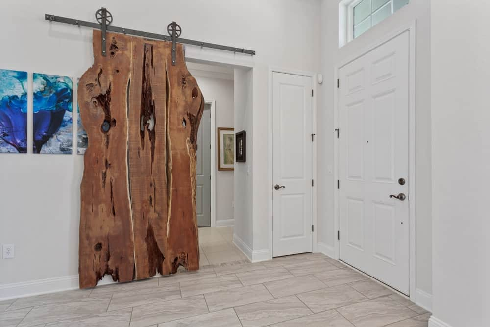 The highlight of this foyer that has white wooden doors, white walls and white marble floors is clearly the rustic Farmhouse-style wooden sliding door on the side of the main door. It stands out against the light elements of the foyer.