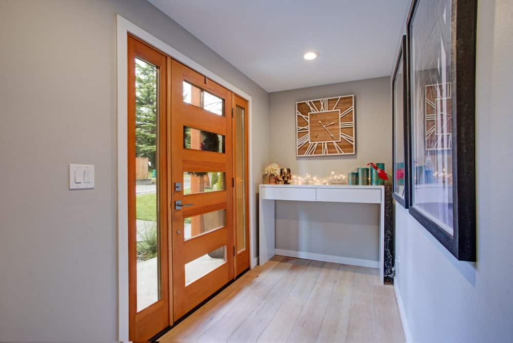 The wooden main door and its side lights are dominated by the charming glass panels that bring in natural lights to the light gray walls of this hallway-like foyer. The far wall by the door is adorned with a white console table bearing decors.