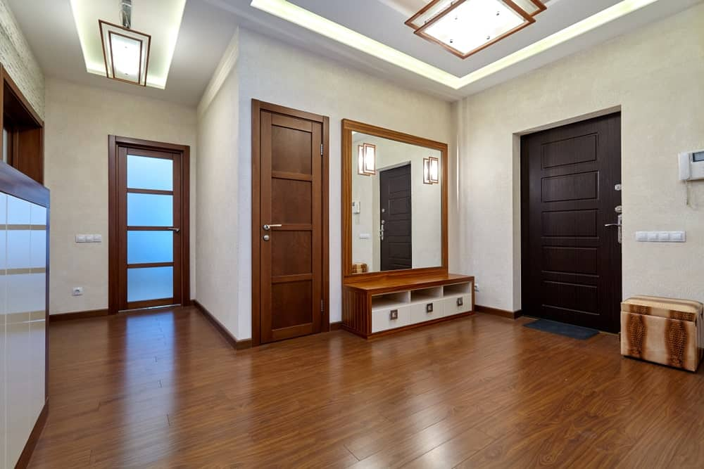 The brilliant white tray ceiling of this foyer has a modern two-tier lighting with a white frosted glass that brightens the white walls and hardwood flooring. This blends with the small mudroom on the right of the dark wooden main door.
