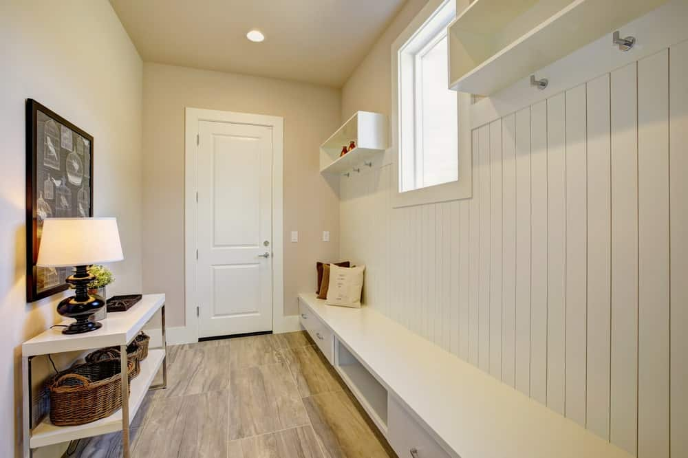 The white main door leads the way to this foyer that has a welcoming mudroom that has a white wooden long built-in bench with walls that has a white shiplap finish. This is topped with a couple of shelves flanking a bright window.