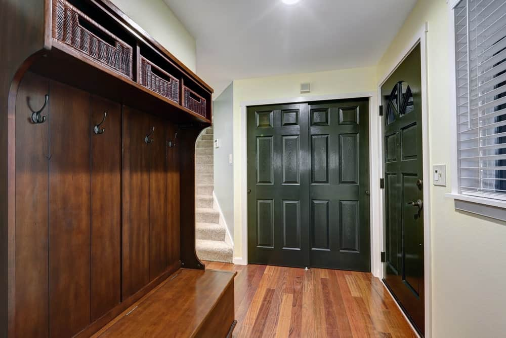 The beautiful green wooden doors of this foyer opens up to the hardwood flooring that matches with the wooden mudroom that has a built-in wooden bench, a row of hooks for the coats and a shelf above it for the baskets.