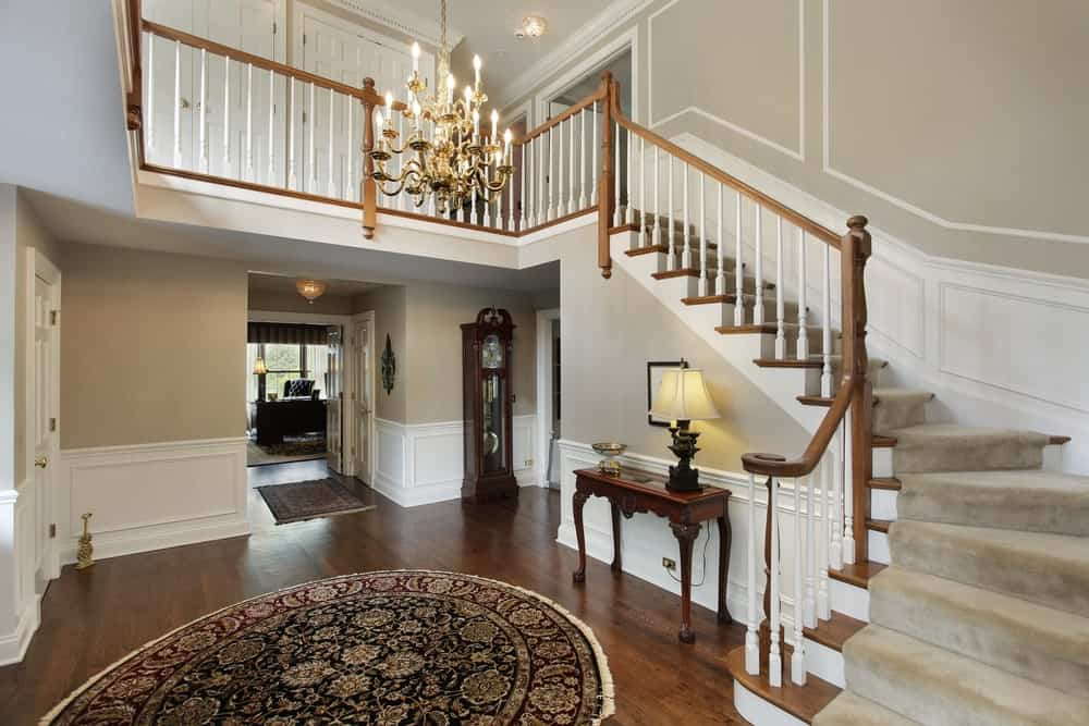 The dark hardwood flooring of this Farmhouse-style foyer is dominated by a large circular colorful patterned area rug. This is topped with a high white ceiling that supports a majestic golden chandelier.