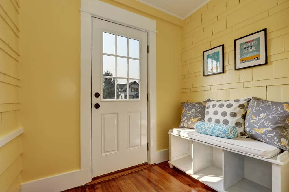 The cheerful yellow walls of this simple Farmhouse-style foyer is made of exterior wall shingles for a unique textured aesthetic. This is adorned with framed artworks and brightened by the natural lights coming from the glass panel of the white wooden door.