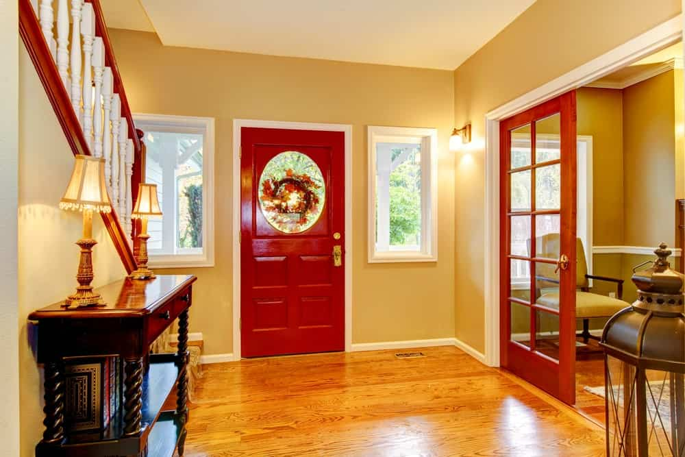 The delightful red wooden main door is flanked with windows that stand out against the beige walls that are warmed by the yellow lights of the wall-mounted lamp. There are also yellow lights from the table lamps on the wooden console table.