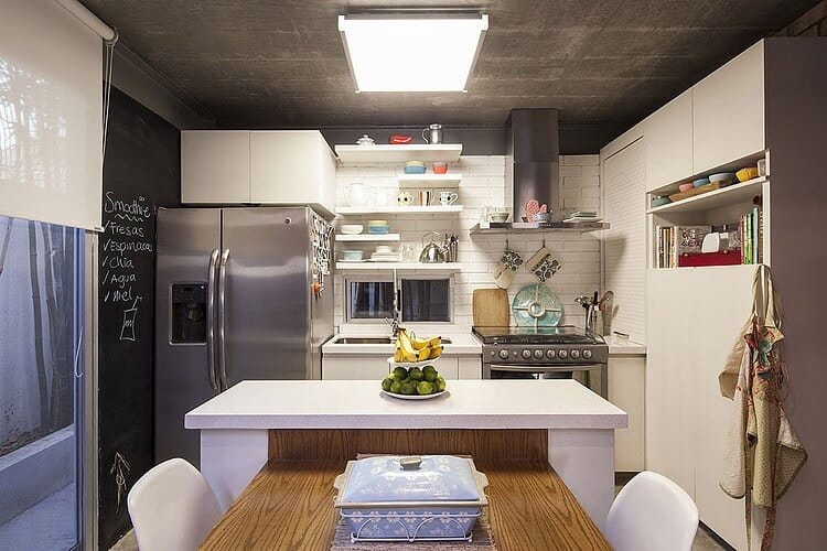 The small and homey industrial kitchen has a white kitchen island that has wooden table attached to it serving as a dining table. The white peninsula is dominated by the large fridge that matches with the gray concrete ceiling.