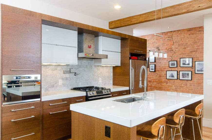 This industrial-style kitchen has a wooden kitchen island that matches with the wooden peninsula with the same thick white countertop. This aesthetic is augmented by the exposed wooden beam of the ceiling and the brick wall on the right.