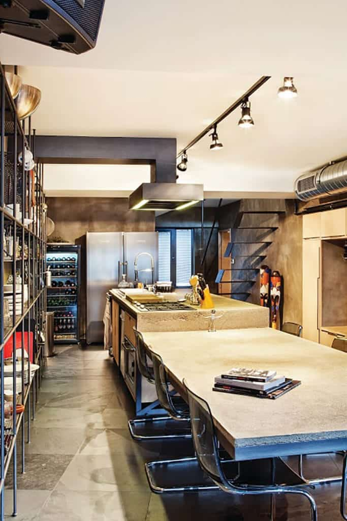 The kitchen island is made of concrete gray materials that extend to an attached dining area. This matches with the concrete flooring and walls that are dominated by a large shelving for storage complemented by the exposed vents of the ceiling.
