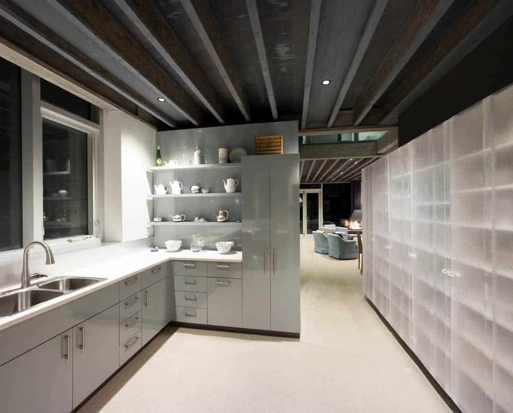 This kitchen has modern elements on its sleek kitchen cabinets and drawers of the L-shaped peninsula that has a light gray hue that complements the white countertop and walls. This is contrasted by the dark industrial-style ceiling that has exposed metal beams.