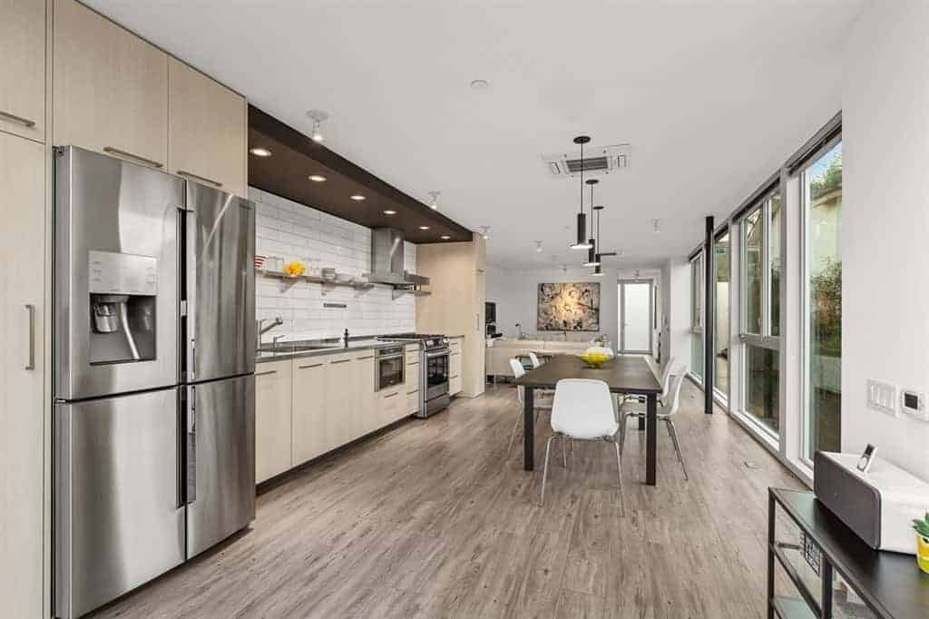 The kitchen peninsula's light gray countertop matches with the stainless steel appliances and complements the white backsplash arranged in a brick wall pattern that is contrasted by the dark wooden panel on the ceiling with recessed lights over the cooking area.
