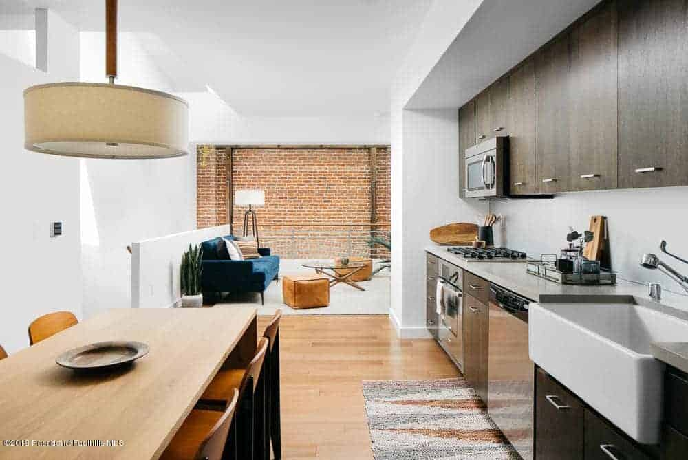This small kitchen is right beside the informal dining area that has the same wooden table as the hardwood flooring. The dark brown cabinets of the peninsula stands out against the white ceiling and has a nice background of a brick wall.