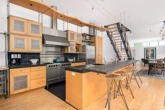 The light hardwood flooring of this industrial-style kitchen matches with the wooden kitchen island and small peninsula that is dominated by the large stainless steel appliances and vent hood of the oven that goes to the white ceiling.