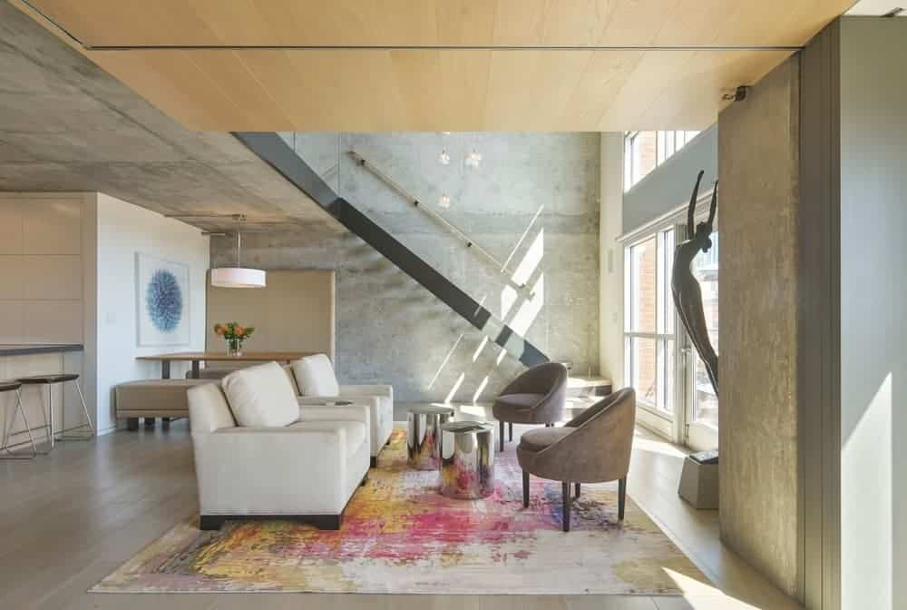 The colorful and chic painting-like large area rug that covers the hardwood flooring provides a nice dash of color for the industrial-style living room and its concrete ceiling and walls matching the cushioned chairs and white sofas.