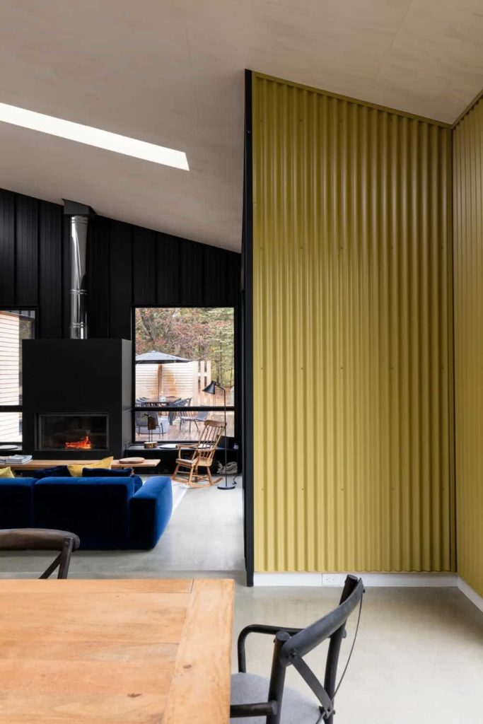 There are yellow patterned metal walls leading to this industrial-style living room that has black walls made of what looks like roofing materials. This matches with the black housing of the fireplace facing the blue velvet cushioned sofa.