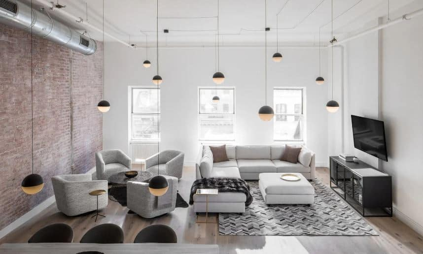This is a large and airy living room with a high white ceiling adorned with exposed pipes, stainless steel vent and the multiple spherical pendant lights hanging over the L-shaped sectional sofa beside a sitting area with four cushioned armchairs.