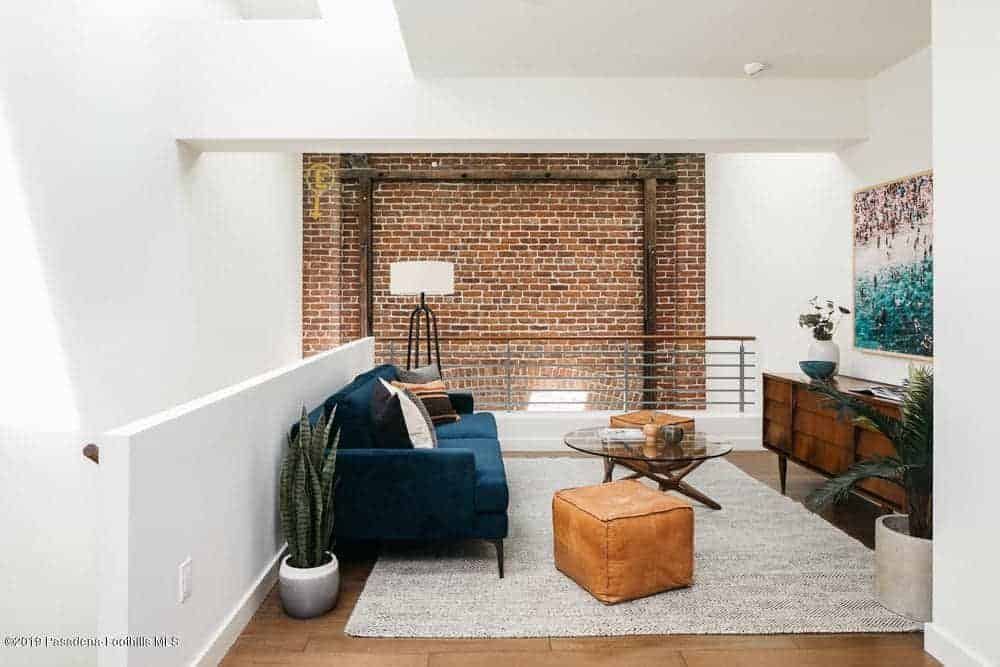 This second floor living room is beside the staircase on one side and adjacent to it is a railing with a background of a red brick wall that stands out against the white walls and ceiling accented with a colorful painting across the green velvet sofa.