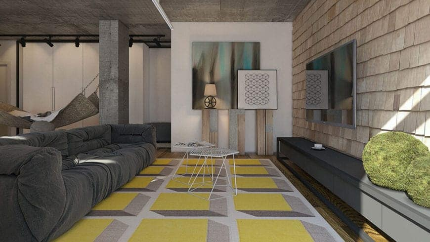 The yellow patterned area rug provides a bright colorful contrast to the gray sofa that matches with the gray concrete ceiling. This sofa faces a wall made of exterior wall shingles that provides a complex contrast to the mounted TV.