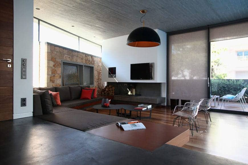 The large L-shaped dark brown cushioned sofa follows the lay of the walls with one wall made of beige stone while the other is a smooth white that houses the TV and the fireplace. These are all under a high wooden shed ceiling.