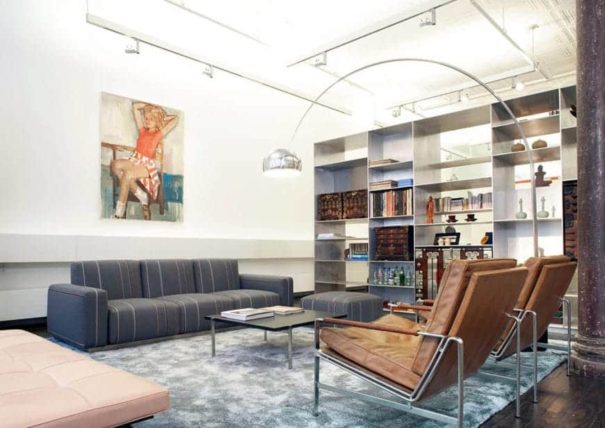The high white ceiling is filled with exposed pipes, tubing and wiring for the brilliant white lights that make the ceiling and walls glow. These walls are adorned with a large painting and a large open shelving that gives the cushioned sofa set a nice complex background.