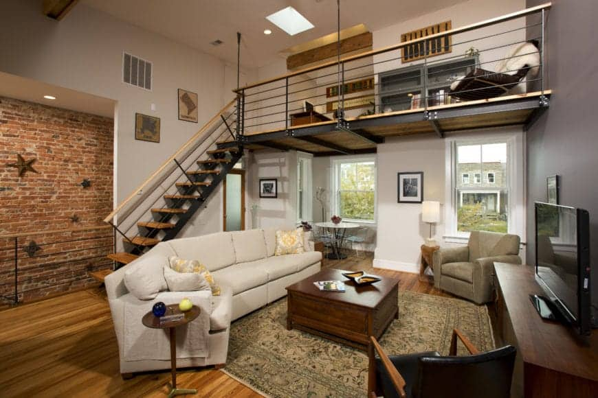 This appears to be a traditional-style living room that is framed with industrial-style elements like the red brick wall adorned stars, the metal staircase leading to a metal loft above that forms a small ceiling above the living room with exposed metal beams.