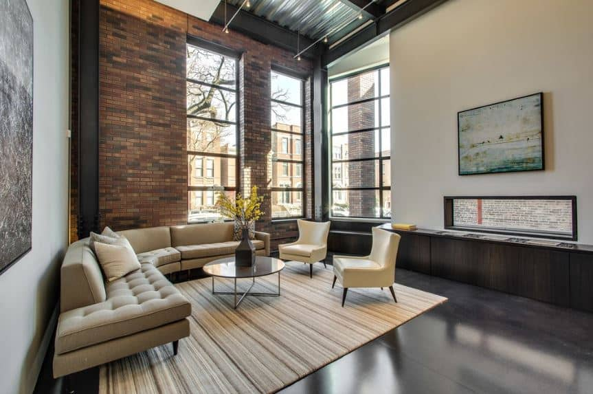 The tall red brick walls of this industrial-style living room is paired with tall windows that bring in an abundance of natural lights to the dark industrial-style flooring that is covered with a beige patterned area rug matching the sofa set.