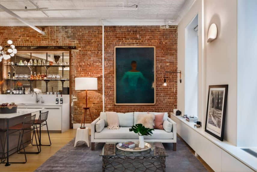 The red brick wall that contrasts the white ceiling that has subtle patterns on it as well as exposed pipes and tubes. This is matched by an off-white two-seat sofa that faces a glass-top coffee table over a dark gray area rug.