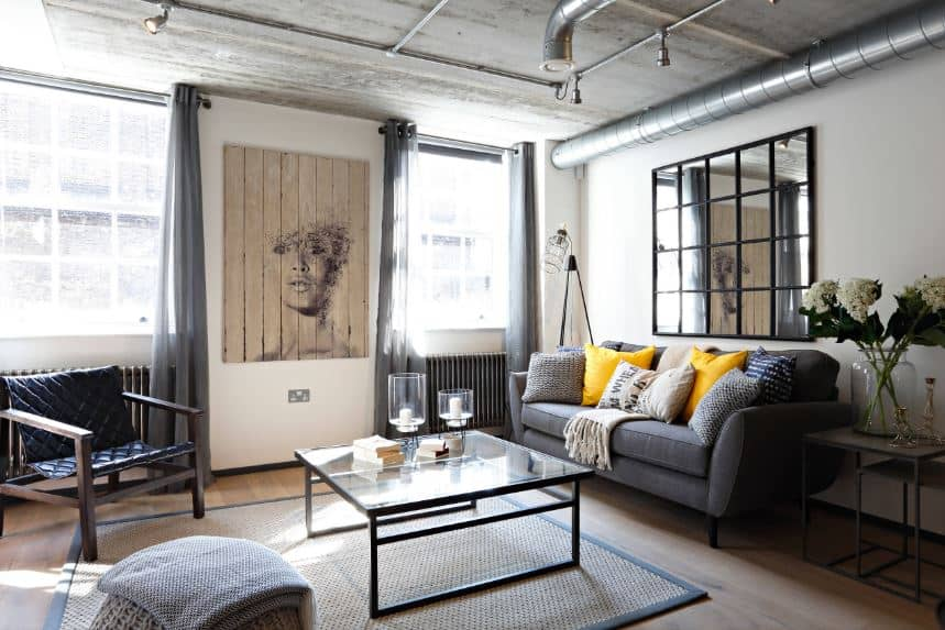 The simple living room that has a dark gray two-seat sofa and a glass-top coffee table over a woven area rug has a ceiling of concrete gray with exposed pipes for the wiring of the spot lights as well as exposed air ducts.