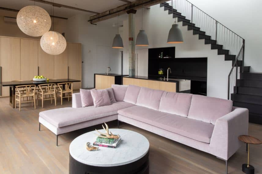 The light pink velvet cushioned L-shaped sofa is the stand-out element of this industrial-style living room that has a hardwood flooring with a round coffee table that has the same white hue as the ceiling with exposed wooden beams and pendant lights.