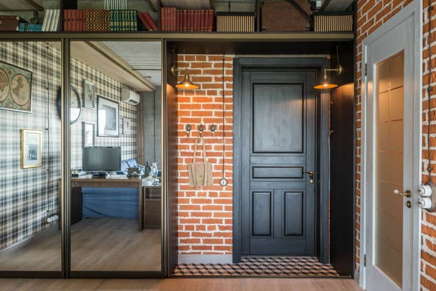 This charming and homey industrial-style foyer has wall-mounted lamps flanking the dark wooden door complemented by red brick walls with the vertical space maximized through book shelves.