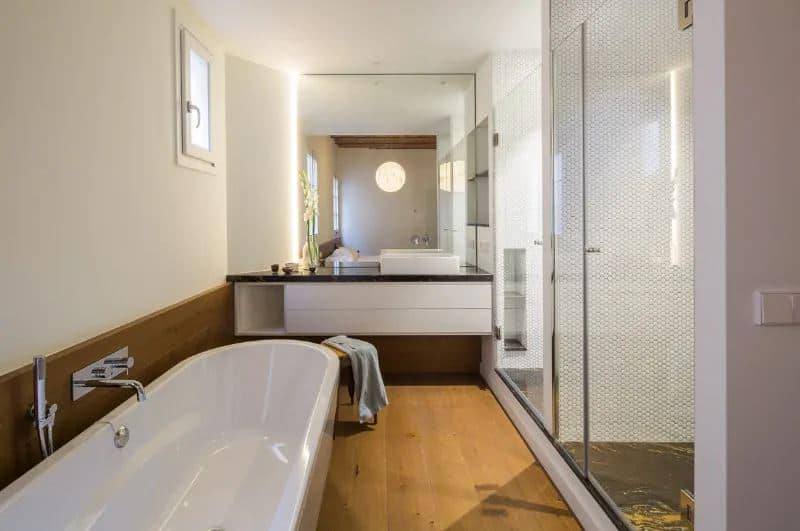 This simple bathroom has a long elliptical freestanding bathtub that stands out against the brown hue of the flooring and backsplash. Across from this are two glass-enclosed shower areas with small tiles on its walls and black marble on its flooring.