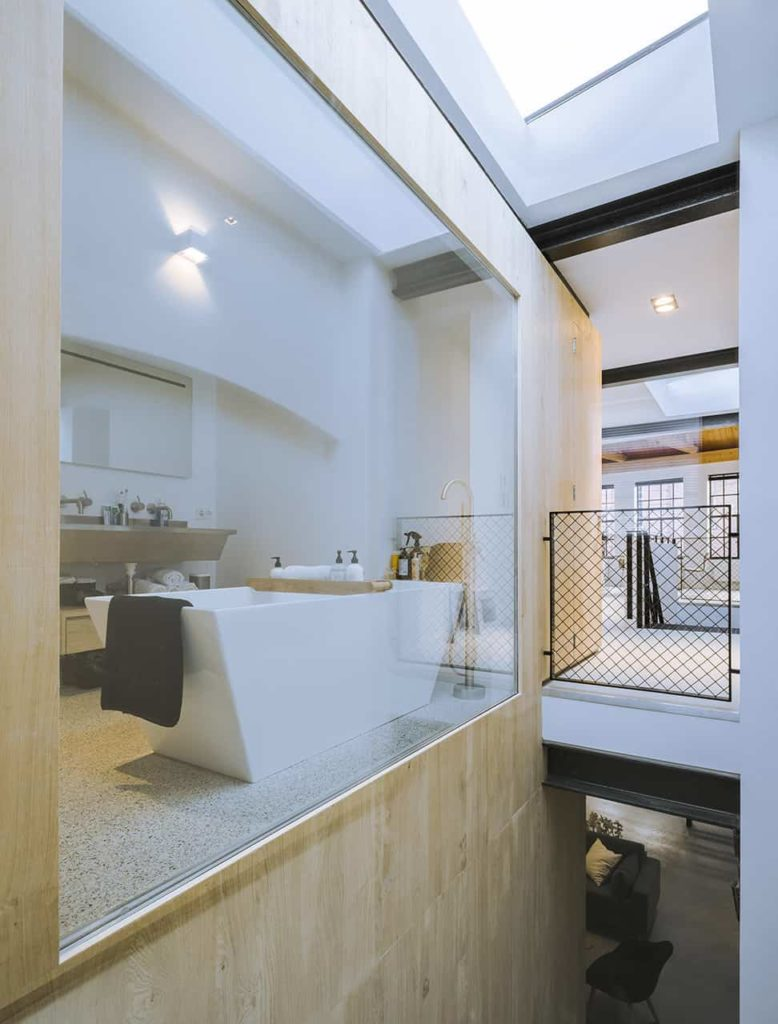 The simple bathroom can be clearly seen from the staircase through its glass wall. It has a white freestanding bathtub across from the gray floating two-sink vanity with exposed pipes underneath that matches the faucets.