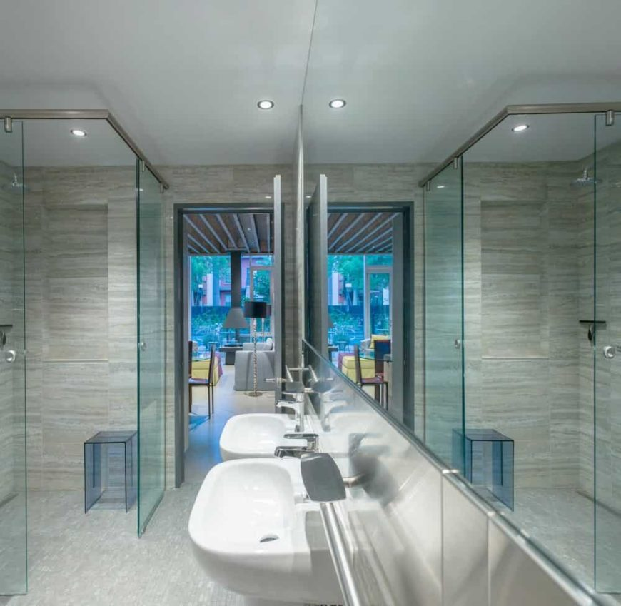 This bathroom has two floating white sinks with stainless steel faucets complementing the large vanity mirror embedded into the wall. This works well with the glass enclosure of the shower area that has gray flooring tiles.