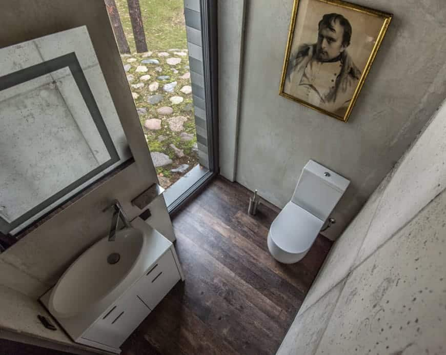 The white modern toilet and floating white vanity stands out against the gray concrete walls accented with a classic painting above the toilet and a wall-mounted vanity mirror above the white sink. The dark hardwood flooring is illuminated by the tall and narrow glass window beside the toilet.