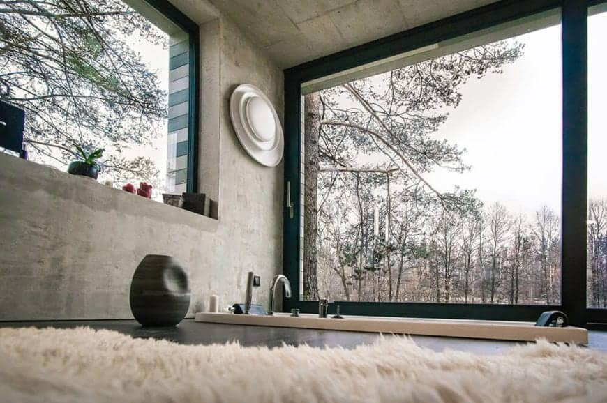 This industrial-style master bathroom has a bathtub embedded into the black flooring that is complemented by the gray concrete walls and ceiling. These are all illuminated by the natural lights coming in from the wide glass windows.