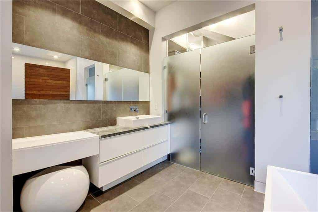 The gray industrial-style flooring and wall have tiles that look like concrete arranged in a brick wall pattern. This serves as a nice contrast to the white modern floating vanity that is paired with a spherical stool across from the white bathtub.