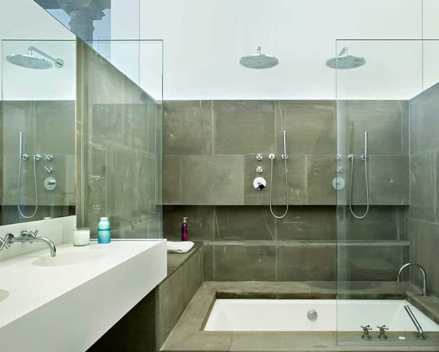 The white floating sink of this industrial-style bathroom matches with the white bathtub that is embedded into gray concrete that extends to the walls of the shower area that has a half glass wall and overhead shower head.