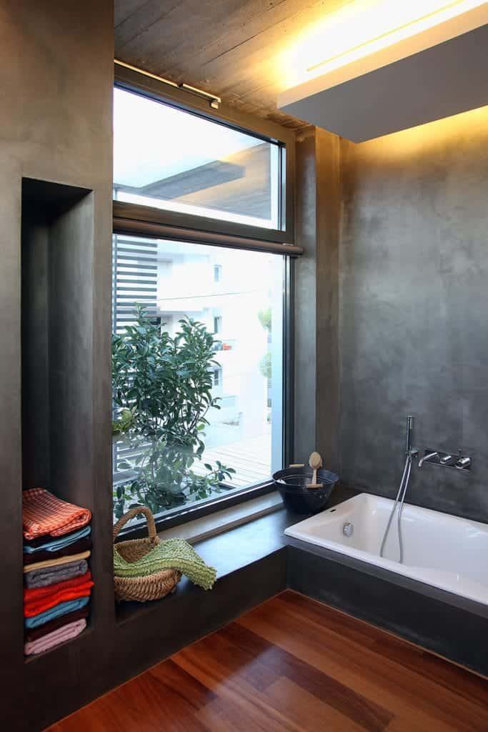 This simple bathroom has gray concrete walls that houses the white bathtub and built-in shelves. This matches with the gray concrete ceiling that has a white wooden panel over the bathtub that has lighting.