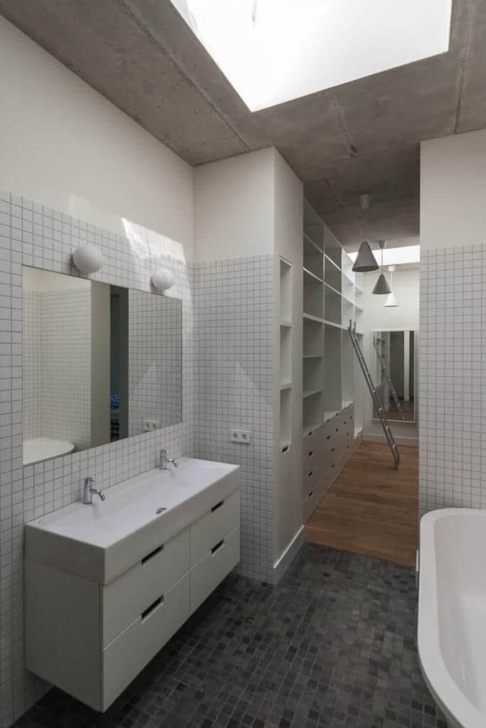This simple bathroom has small tiles on its walls and flooring. The flooring has various shades of gray while the walls have only white tiles. These are complemented by the gray concrete ceiling that has a skylight over the white bathtub and vanity.