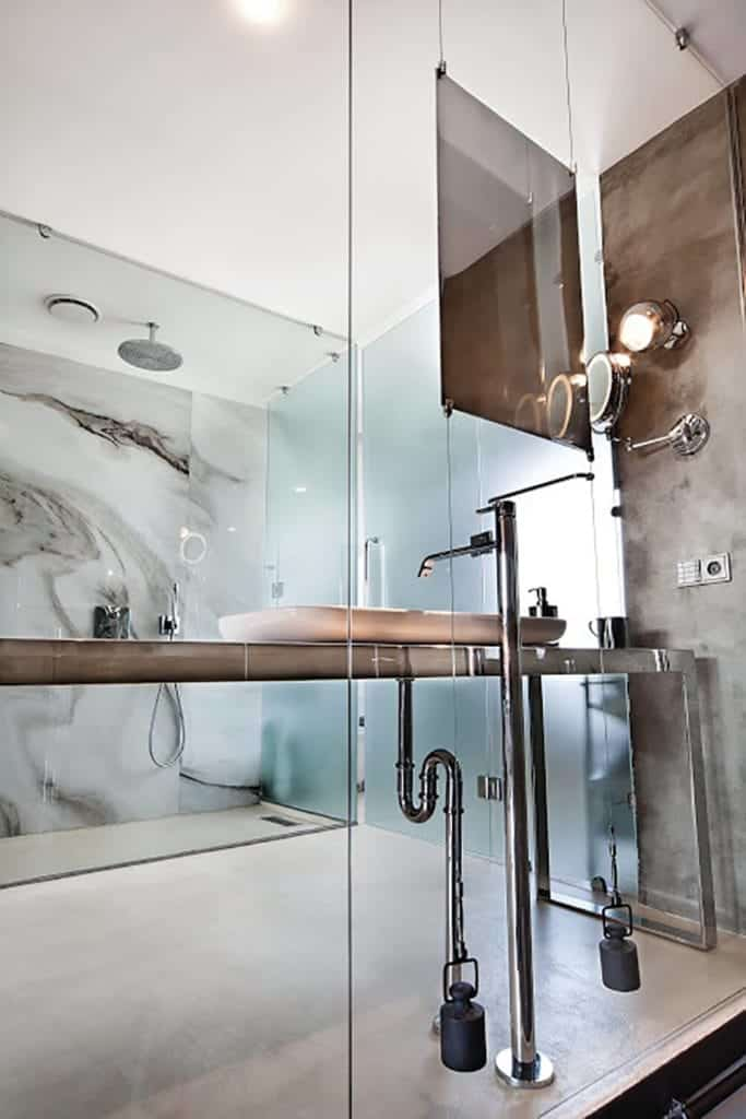 This bathroom is seen from the outside through a glass wall. It has a gray concrete flooring that complements the stainless steel vanity and the pipes of the white sink as well as the fixtures of the glass-enclosed shower area across.
