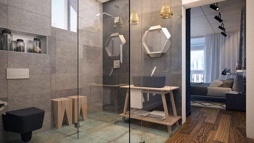 The hardwood flooring from the bedroom leads to this bathroom with a glass enclosure. Within this glass enclosure is the sink with a wooden table and black basin matching the black bowl and wooden stools of the shower area.