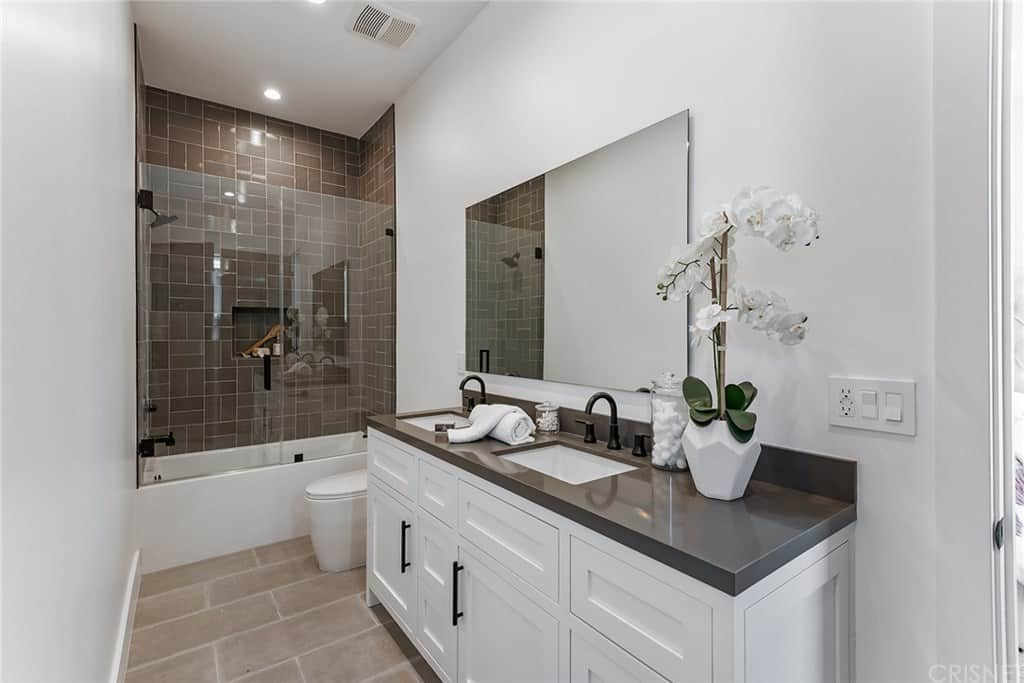 This is a simple Farmhouse-style bathroom with a glass enclosed shower area at the far wall with gray wall tiles arranged in a brick wall pattern. Beside this is the white porcelain toilet that is complemented by the beige flooring tiles as well as the white wooden vanity with a dark gray countertop.