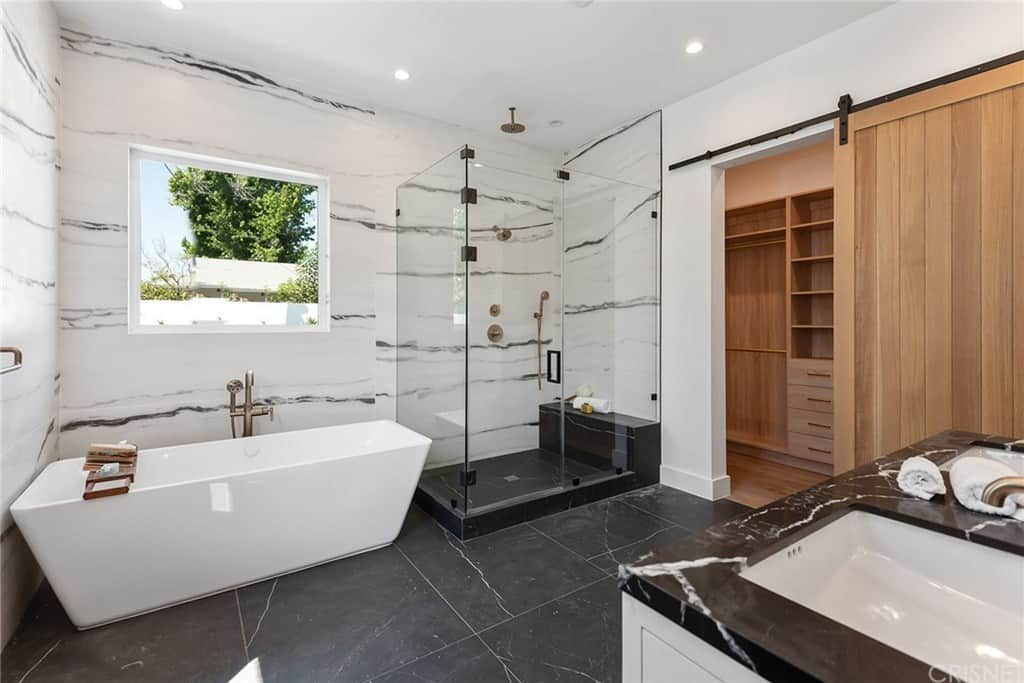 The white marble walls are contrasted by the black marble flooring tiles that makes the freestanding bathtub stand out. This tub has a brass faucet that matches with the fixtures of the glass-enclosed shower area next to a wooden sliding door to the closet.