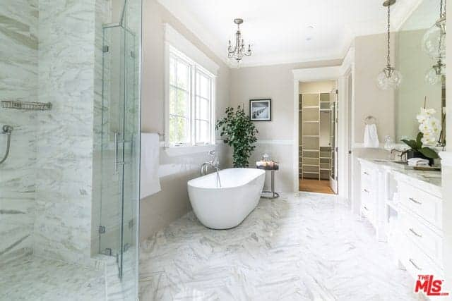 This Farmhouse-style master bathroom has white marble flooring that extends to the walls of the glass enclosed shower area. Beside this is the freestanding bathtub brightened by the window and topped with a charming chandelier.