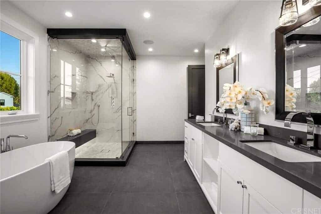 The dark gray countertop of this master bathroom matches with the dark gray tiles of the flooring. This is then contrasted by the white freestanding bathtub and the white wooden vanity that has shaker cabinets and drawers topped with vanity mirrors.