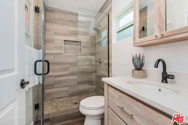 The walls of the glass enclosed shower area of this Farmhouse-style bathroom has tiles that look like wood. This works well with the wooden mirrored medicine cabinet and vanity with wooden drawers and a white countertop that houses a white sink and its black faucet.
