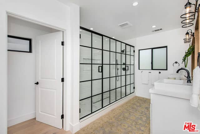 This master bathroom has a wide shower area enough for two within its glass wall that has black frames that matches with the window and the fixtures of the shower area and vanity area. This has a white sink topped with a wood-framed mirror.