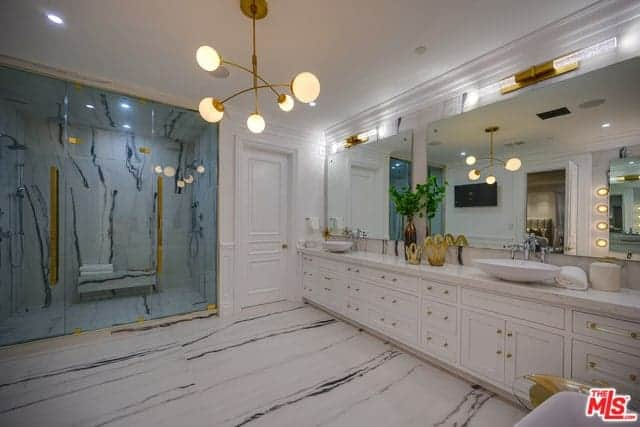 The wide white ceiling of this Farmhouse-style bathroom is adorned with a golden decorative modern chandelier with spherical lights. The golden hues of this lighting matches with the handles of the white wooden two-sink vanity as well as the handles of the shower room glass doors.