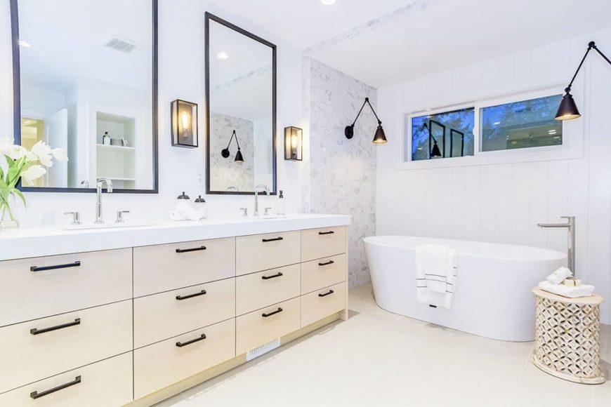 The bright white freestanding bathtub, walls and ceiling of this Farmhouse-style bathroom is complemented by the beige wooden vanity that matches with the flooring and the stool beside the bathtub. These are augmented by the dark wall-mounted lamps.